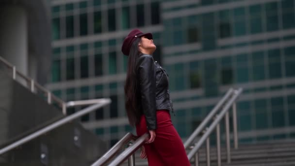 a beautiful dark-haired female model in a purple cap and leather jacket, in a red dress poses in a public place near the building on the stairs. Located on one of the streets of the city.