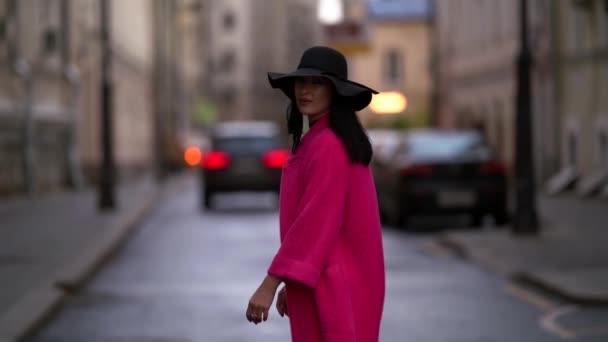 Eine Frau mit schwarzem Hut und lila Mantel geht selbstbewusst auf die Straße in einer überfüllten Stadt. Es liegt auf einer asphaltierten Straße vor dem Hintergrund von Autos und Häusern, ein Blick von hinten.