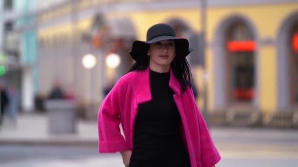 Eine modische Frau mit schwarzen Haaren, schwarzem Hut und lila Mantel geht selbstbewusst auf die Straße in einer überfüllten Stadt.