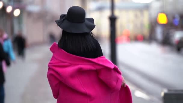 Modisch glamouröse junge Frau mit schwarzen Haaren, schwarzem Hut und lila Mantel geht die Straße in der Stadt entlang, lächelt und posiert. Der Blick von hinten.