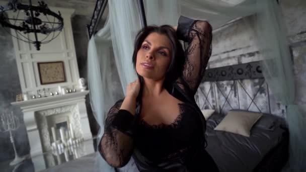 Hezká brunetka v černé krajkové kombinéze pózující v pokoji u postele. Vynikající štíhlé a tónované tělo. Koncept erotiky.