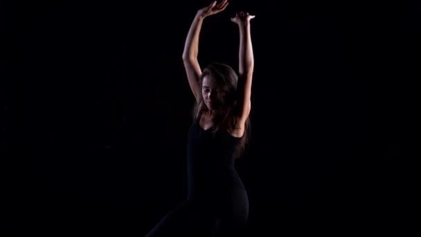 eine junge schlanke Frau im schwarzen Anzug in einem Studio vor schwarzem Hintergrund tanzt, bewegt und posiert.