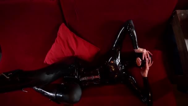 anonymous excited woman dressed black latex suit with full face mask for bdsm role play, lying on couch