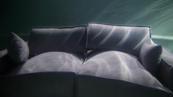 Detailní záběr šedé pohovky s polštáři, která je pod vodou, odráží světlo z vln.