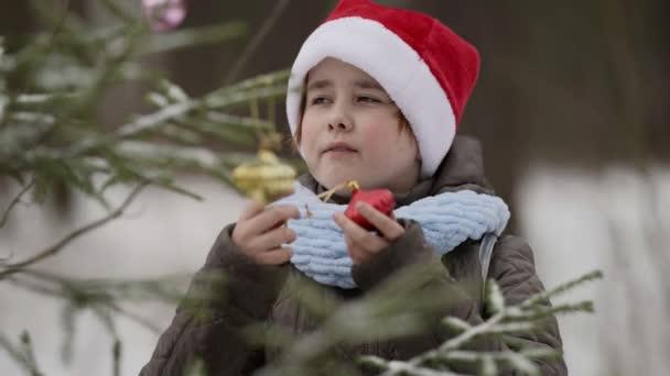 niedliche kleine Mädchen schmückt Weihnachtsbaum im Freien, trägt rote Weihnachtsmütze und wartet Wunder