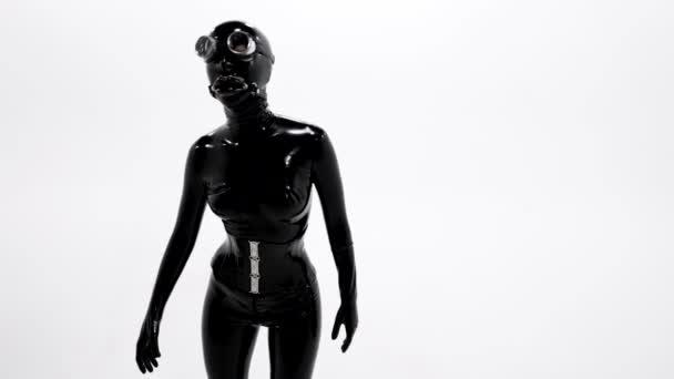 Porträt einer üppigen Po-Frau in schwarzem Latex-Anzug und Gesichtsmaske mit Knebel, die sich langsam bewegt