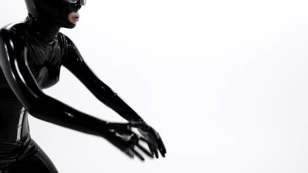 aufgeregte Tänzerin trägt schwarzen Latex-Anzug und Gesichtsmaske, Bdsm-Thema und Sexfetisch