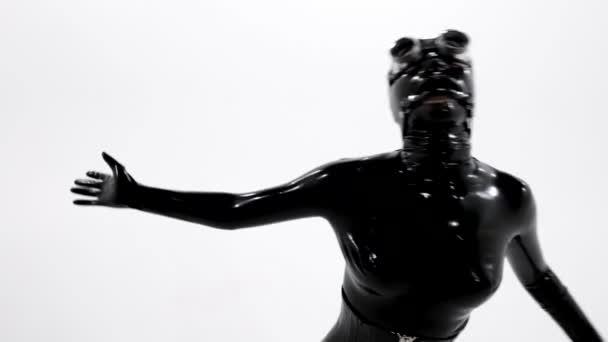 Sklavin im schwarzen Latex-Anzug tanzt im weißen Studio, Rollenspiel mit Kleidung und Accessoires