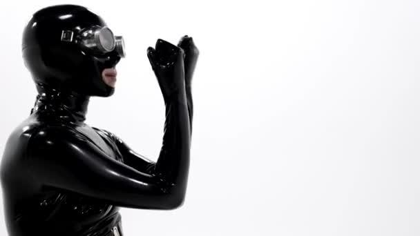 Porträt einer Frau in einem engen schwarzen Latex-Anzug für ein BDSM-Rollenspiel, auf ihrem Gesicht trägt sie eine Maske, an ihren Füßen Stiefel mit Absätzen, sie posiert auf weißem Hintergrund im Studio.