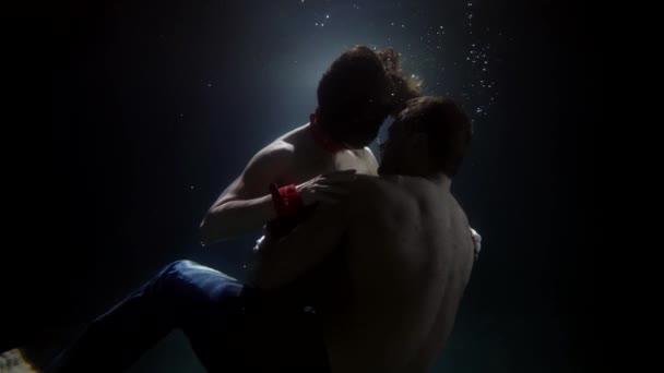 Sinnliches Paar schwimmt und dreht sich unter Wasser. Ein Mann umarmt und küsst leidenschaftlich eine Frau. Es gibt eine Menge Blasen im Umlauf.