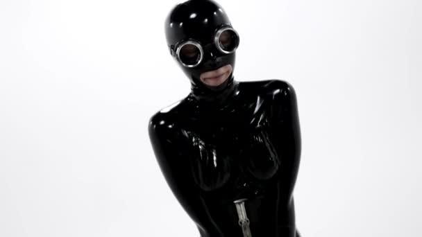 Nahaufnahme einer Frau in einem engen schwarzen Latex-BDSM-Rollenspielanzug, die eine Maske auf dem Gesicht trägt und vor weißem Hintergrund in einem Studio posiert.