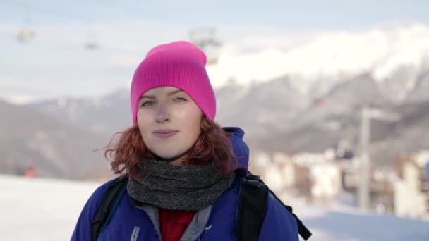 Portré egy aranyos nő rózsaszín kalap és kék kabát áll a háttérben sífelvonók, mosolygós, sétál egy téli napon a háttérben a hegyek. A síközpont koncepciója.