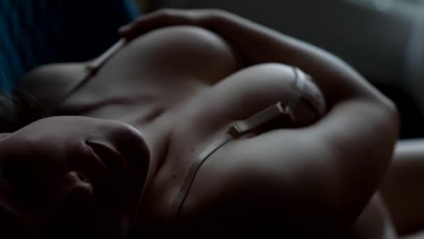 Közelkép egy busty szexi nő fekszik és pózol az ágyon, gyönyörű fehérneműt visel.