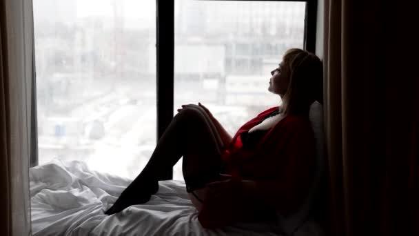 blondýna žena oblečená erotické spodní prádlo a hedvábné šaty sedí na parapetu v bytě ve dne