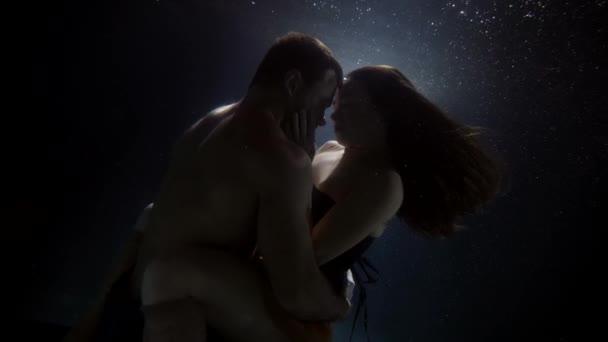 brünette Dame und bulliger Mann umarmen sich im Wasser des Pools, Unterwasserblick