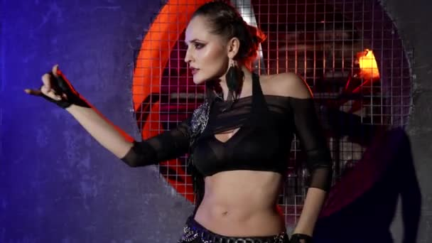 Pretty woman is performing modern version of belly dance in studio, wrigling her body and hands