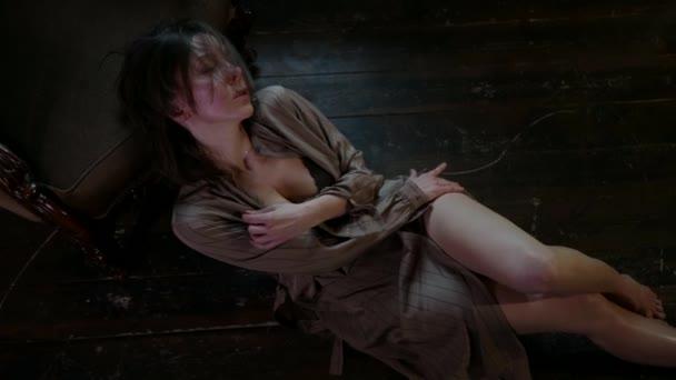 aufgeregte Frau in Dessous liegt auf dem Boden im Zimmer und streichelt ihren Körper, Draufsicht