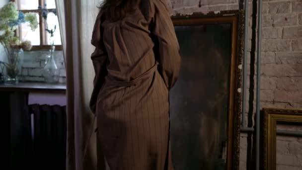 sexy Dame in Dessous tanzt verführerisch im Zimmer und sieht sich selbst im Spiegel an