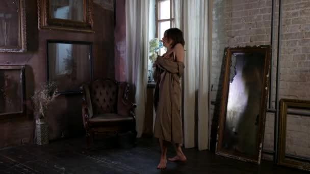 erwachsene Dame trägt Dessous und Seidenkleid tanzt allein im Wohnzimmer mit romantischem Interieur