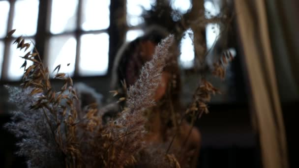romantische Innenaufnahmen einer erwachsenen Frau mit einem Strauß getrockneter Blumen und Blätter