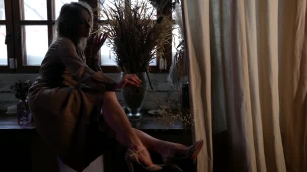 romantische erwachsene Frau ruht zu Hause, sitzt auf der Fensterbank und streichelt ihr Bein