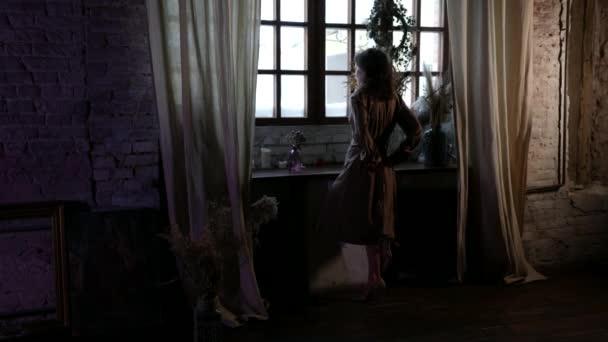 Hausfrau trägt luxuriöses Seidenkleid und blickt zum Fenster des großen Wohnzimmers