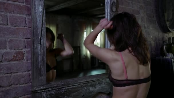 Hausfrau zieht sich aus und tanzt vor Wandspiegel im Zimmer, ruht allein zu Hause
