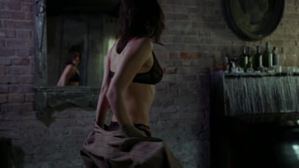 schlanke sexy Frau tanzt vor Spiegel und zieht sich aus, sexueller weiblicher Körper in Dessous