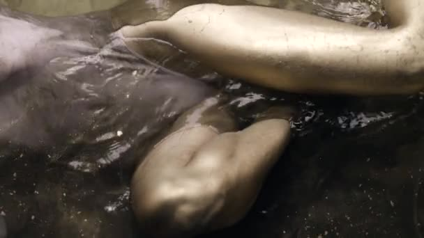 A womans legs and body in a bodysuit with painted golden skin lie in the water, slowly moving and posing.