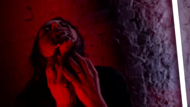 Az ördögi női vámpír egy entitás reinkarnációja a testben. Ijesztő boszorkány arc kísérteties Halloweenkor