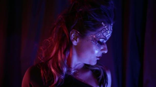 sexy žena tančí ve tmě, jasný make-up na tváři a lesklé krystaly