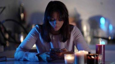 Genç siyah saçlı bir kadın bir masada oturuyor, cep telefonuna bakıyor, önünde çeşitli mumları gevşetiyor. Odada..