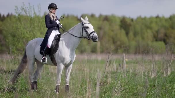 Žokej pózuje na poli na koni. Dívka chodí na ranči s koňmi