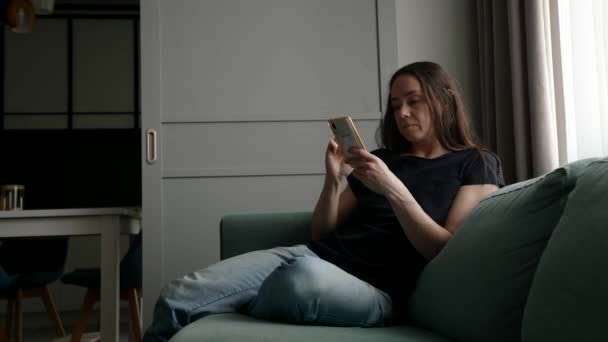 felnőtt háziasszony pihen kanapén okostelefonnal, ül egyedül a nappaliban