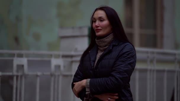 Eine Brünette mit langen Haaren in Strickpullover und dunklem Mantel geht an einem trüben Herbsttag am Zaun eines alten Hauses entlang. Im Hintergrund sieht man die Wände mit abblätterndem Putz aus dem Fokus