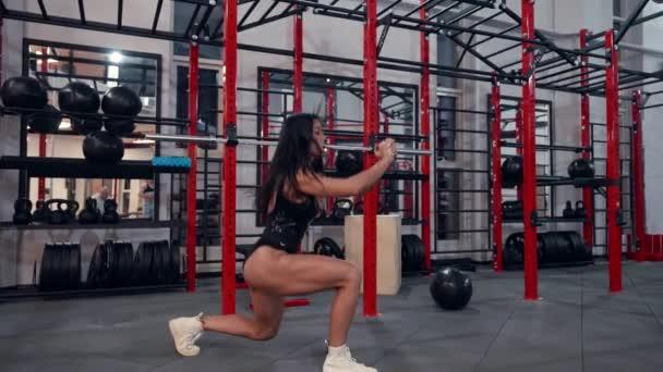 squatting a skákání pro trénink svalů nohou, sexy sportovní žena dělá cvičení v tělocvičně