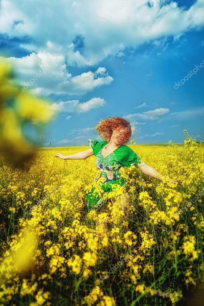 Happy red-haired young girl in a green dress jumping in yellow field