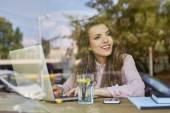žena pracuje na notebooku z kavárny