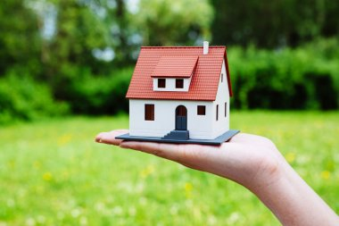 Miniature house held by a person