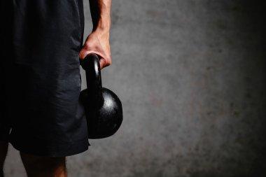 Muscular arm holding a kettlebell