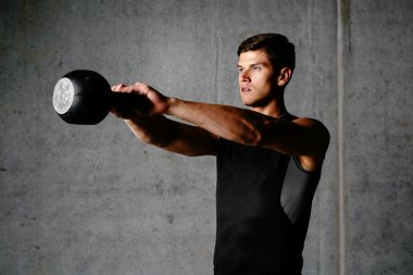 Muscular athlete working out with kettlebell