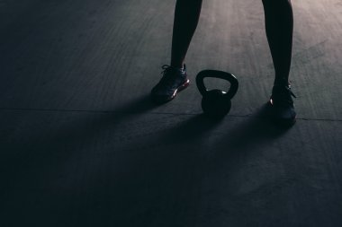 Legs of a bodybuilder with a kettlebell