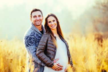 Pregnant couple in wheat field