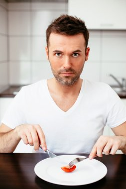 Man eating tiny portion of food