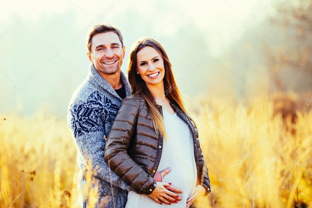 Pregnant couple in wheat field