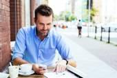 Muž s smartphone na venkovní kavárna