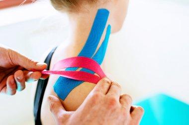 Therapist applying tape to patient shoulder