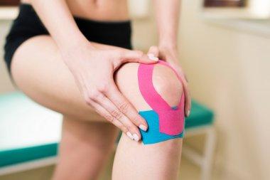 Woman massages injured knee