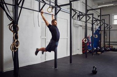 Man at gym exercise Kipping pull-ups