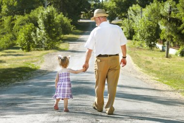Grandfather and granddaughter walking